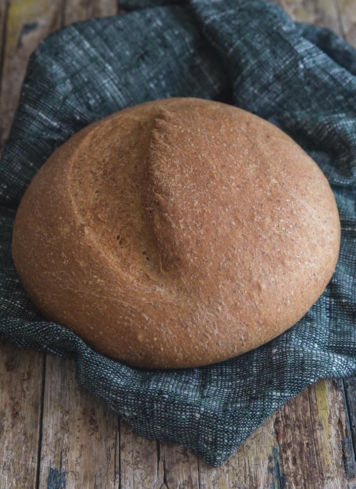 baked whole wheat loaf on a blue napkin
