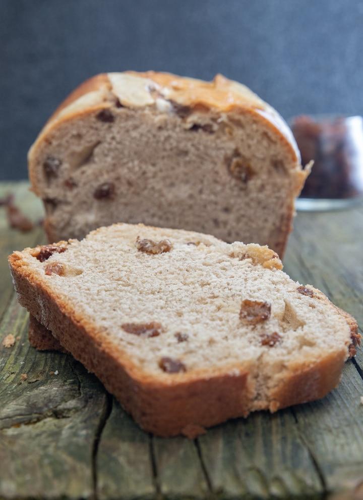 hotcross bun bread on a wooden board with a slice cut.