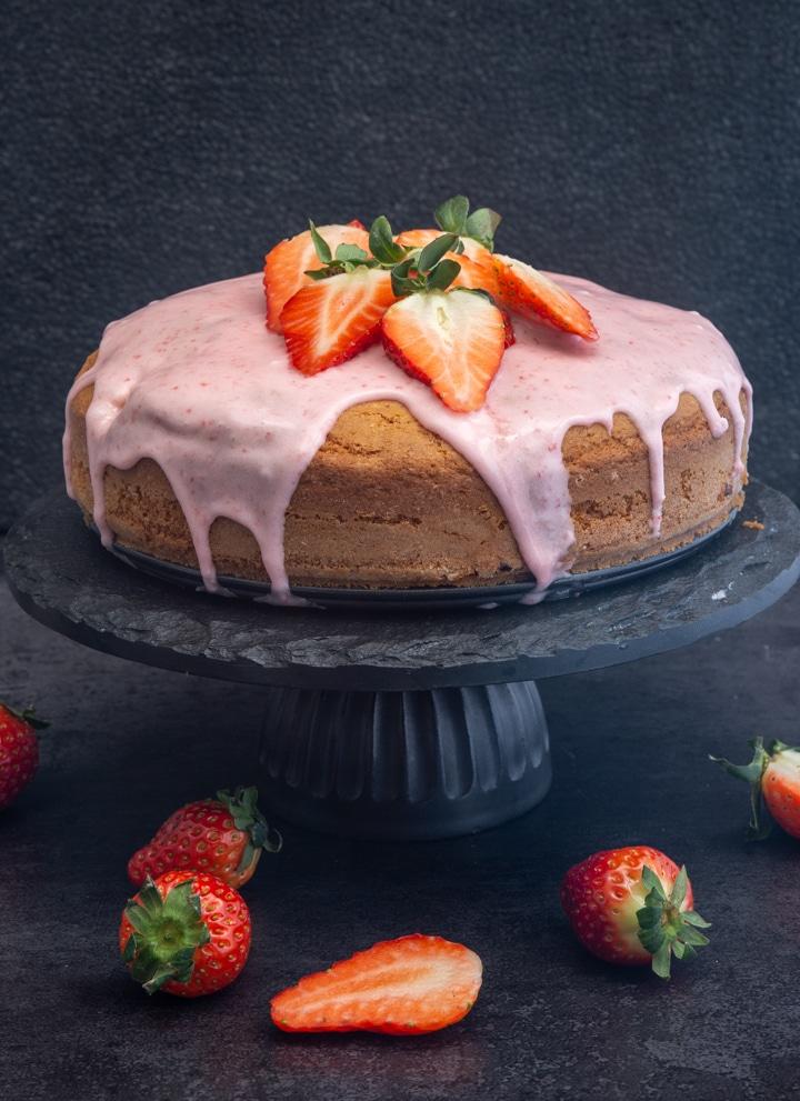 strawberry cake on a black cake stand