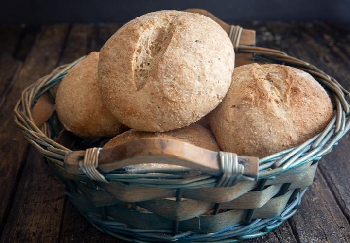 sourdough whole wheat buns in a blue basket.