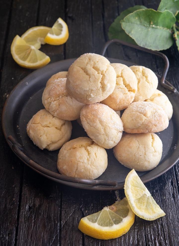 Lemon cookies on a black plate with slices of lemon.