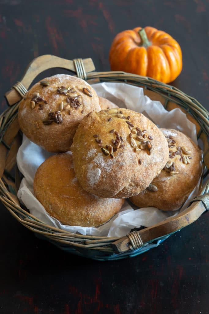 Pumpkin bread buns in a blue basket.